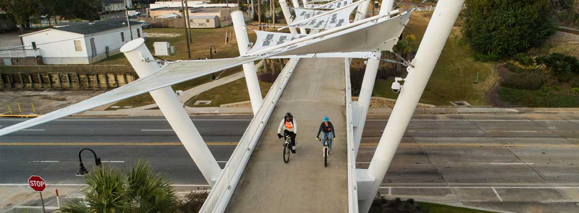 Two bikers trafeling aross the padestrian bridge