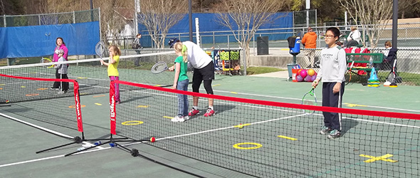 Young people learning to play tennis