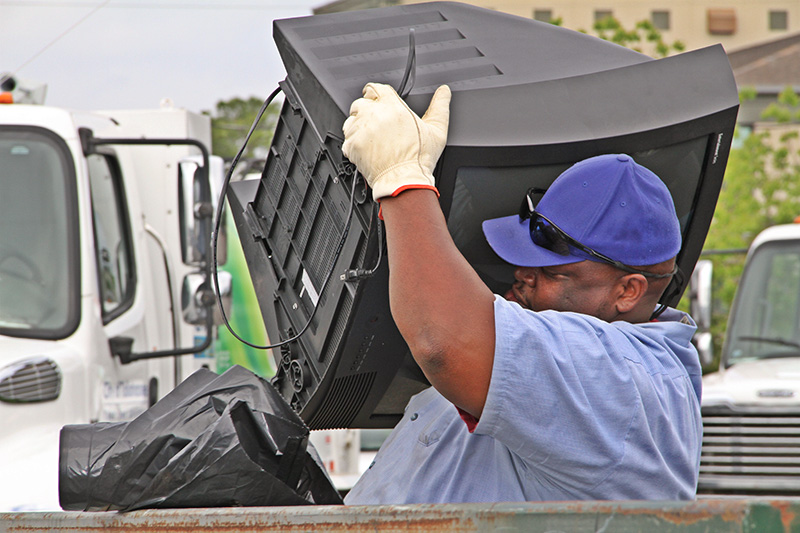 A solid waste worker collects a tv at an annual Cash for Trash event.