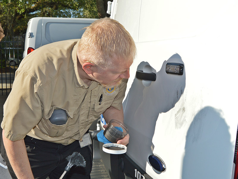 A forensics unit investigator inspects a handprint on a vehicle.