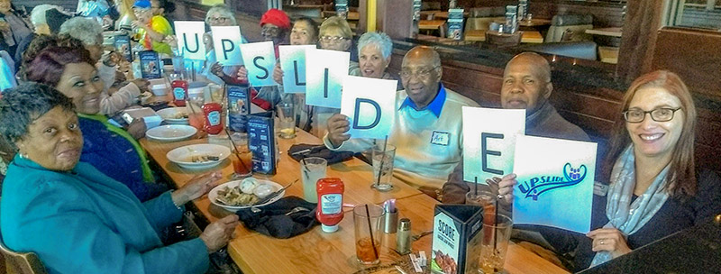 A group of seniors holding up pages that spell UPSLIDE, enjoying lunch together at a restaurant.