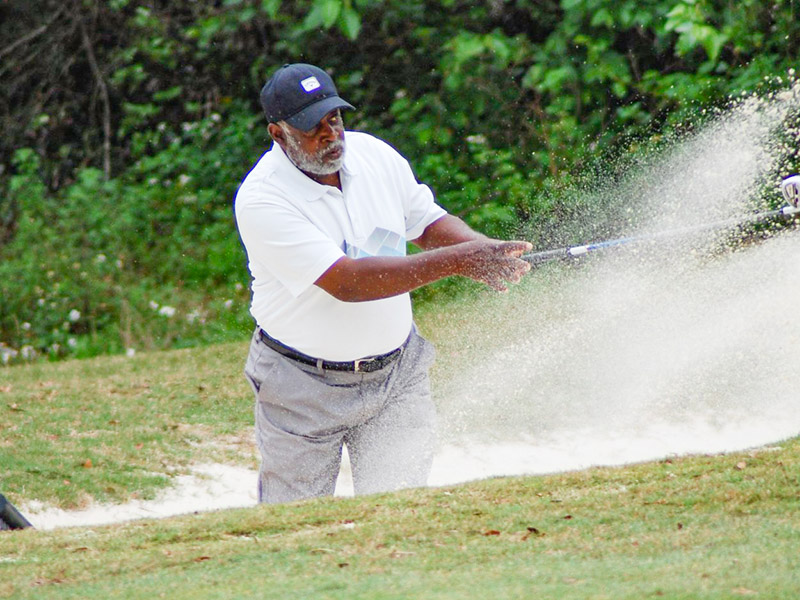 A man hitting a golf ball out of a sand trap.